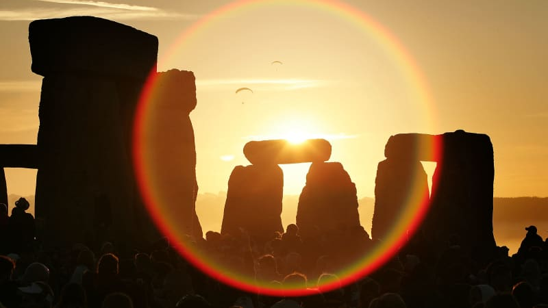 People watch the midsummer sun as it rises over the megalithic monument of Stonehenge.