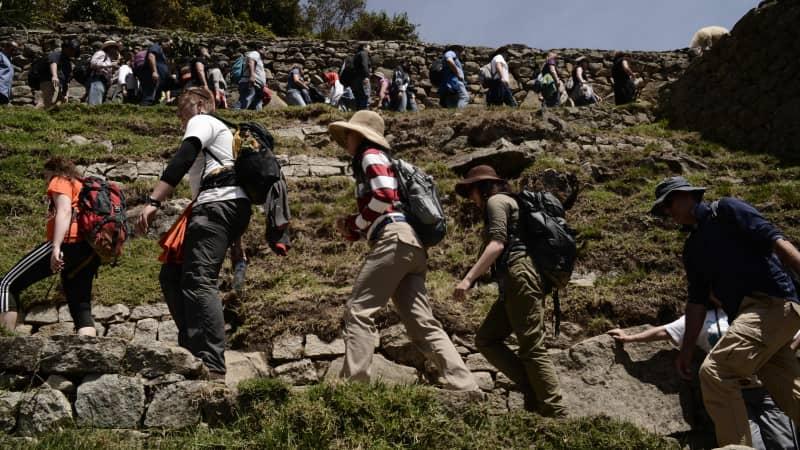 In Machu Picchu, in Peru, crowds of people line up to explore the Inca ruins.