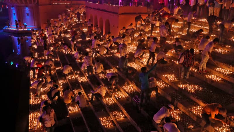 Participants light earthen oil lamps on the banks of the Sarayu river in an attempt to enter the Guinness World Records for the largest display of oil lamps on the eve of Diwali