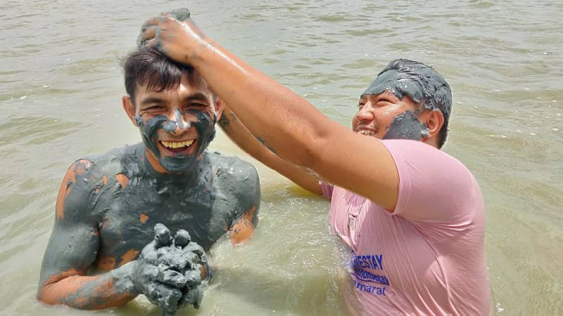Thaksin Minman (left) and Fud Himma (right) demonstrate the mud beauty treatment.