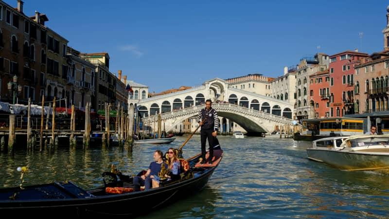 A gondolier glides past the Rialto Bridge, crossing the Grand Canal.