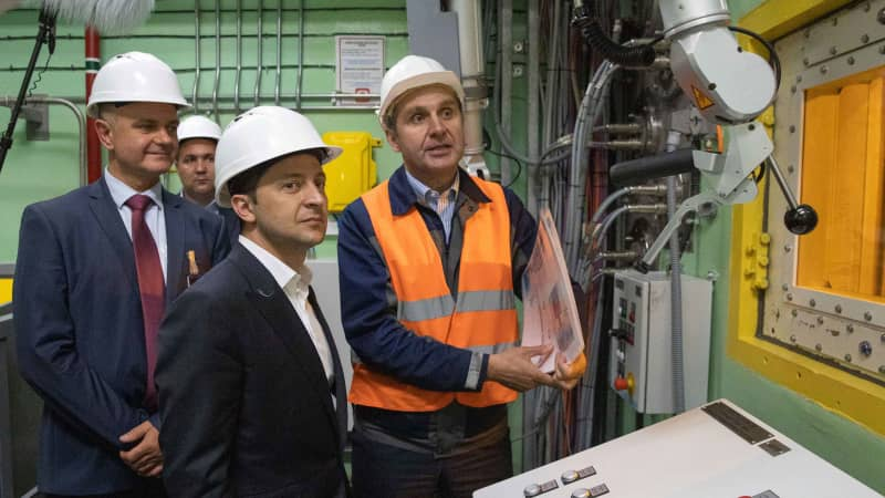 "Ukrainian President Volodymyr Zelenskiy, foreground, visits the ""new safe confinement"" shelter that spans the remains of the Chernobyl nuclear power plant's Reactor No. 4, in Chernobyl(Ukrainian Presidential Press Office via AP)"