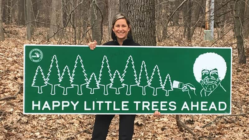 Michigan Parks and Recreation's Michelle Coss with one of the park signs.