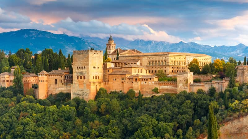 The Alhambra Palace and fortress complex glows during sunset in Granada.