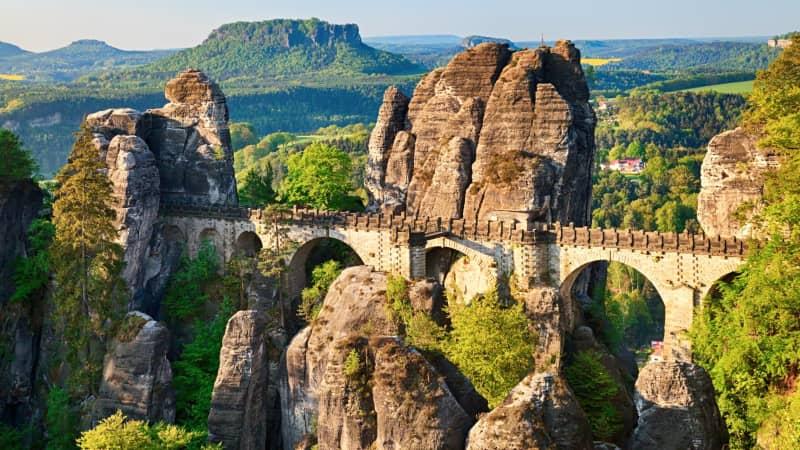 The sun rises over Bastei rocks and the Bastei Bridge in Saxon Switzerland, Germany.