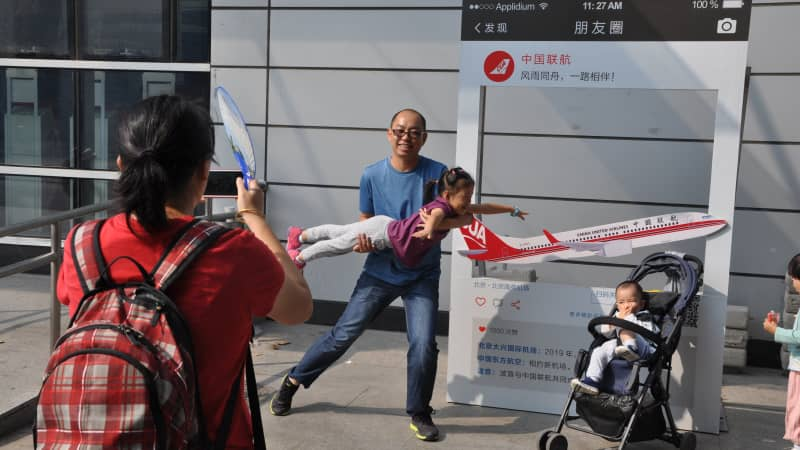 Wang Xiang and his young daughter pose in front of a sign commemorating the closure of Beijing's Nanyuan Airport on September 29.
