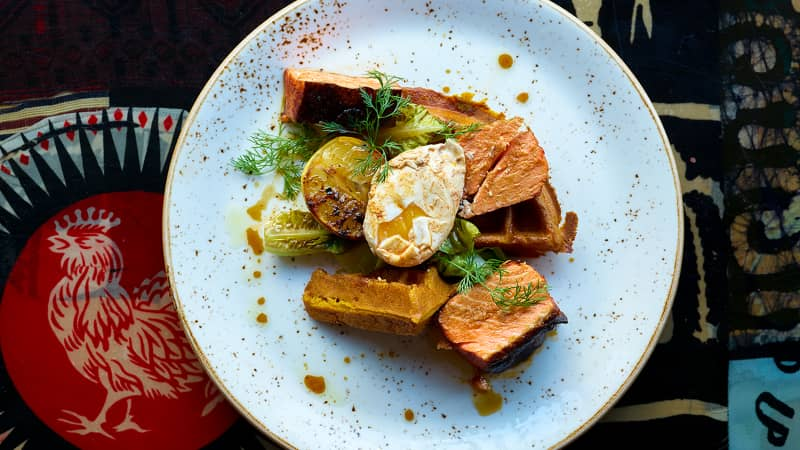 Marcus Samuelsson's Berbere-Smoked Salmon with Sweet Potato Waffles incorporates Ethiopian flavors and spices.