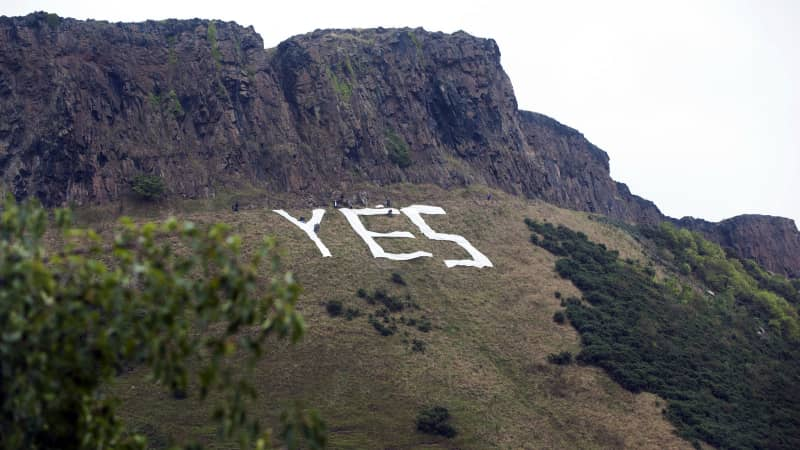 "Pro-independence campaigners place a huge ""Yes"" sign underneath Salisbury Crags in Edinburgh on September 17, 2014, on the eve of Scotland's independence referendum."