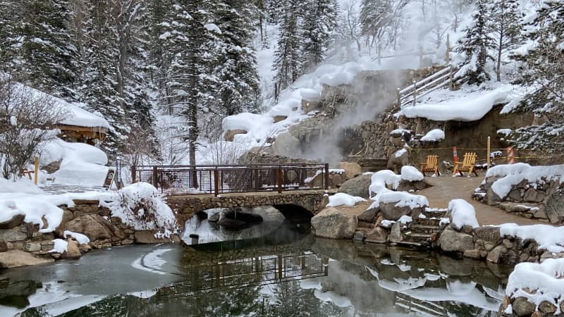 A stone bridge across the icy cold creek leads to the series of hot spring pools.