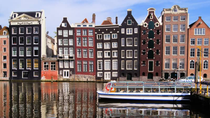 Traditional houses line canals in Amsterdam, the official capital of the Netherlands.