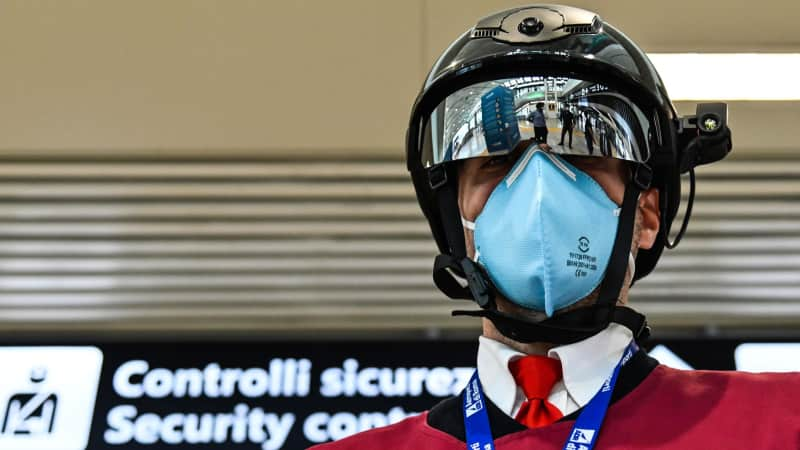 """A Fiumicino airport employee displays a """"Smart-Helmet"""" portable thermoscanner to screen passengers and staff for COVID-19, on May 5, 2020 at Rome's Fiumicino airport."""