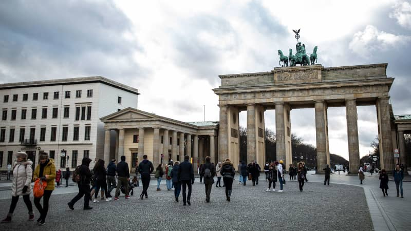 Tourists stand near the Brandenburg Gate on March 13, 2020 in Berlin, Germany