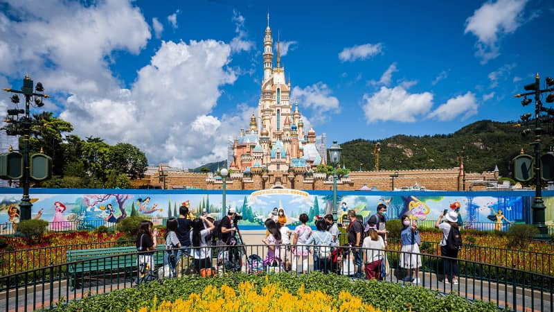 Visitors take photos in front of the Castle of Magical Dreams at Hong Kong's Disneyland on June 18. The California version hopes to reopen on July 17 but has delayed that plan for now.