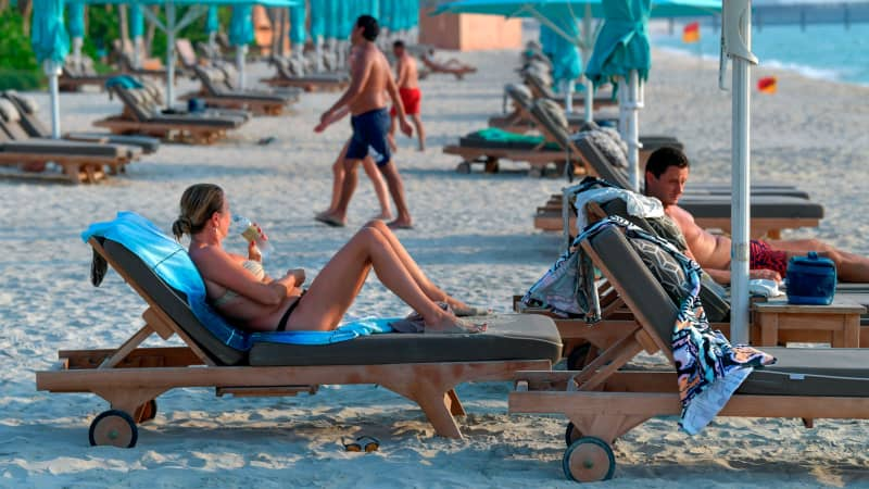 Tourists sunbathe at the beach of the Al Naseem hotel in Dubai.