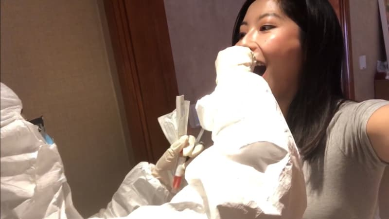 A city worker in protective gear arrived at Wang's apartment to test her for the coronavirus.
