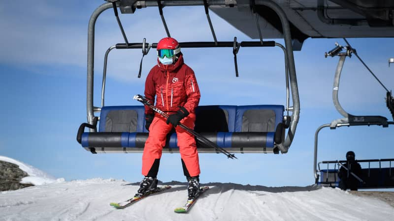 A skier wearing a protective face mask against the spread of the Covid-19, caused by the novel coronavirus, disembarks from a ski lift to hit the slopes during the first snows of the season above the ski resort of Verbier in the Swiss Alps on November 15, 2020