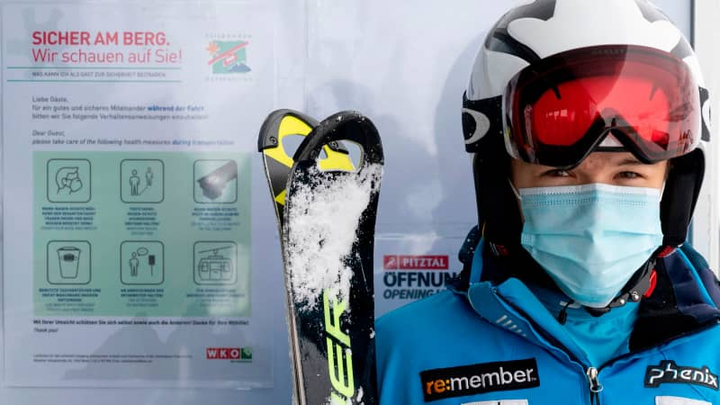 A skier stands next to the covid-19 safety instructions sign at Pitztal glacier, Austria on October 29, 2020.