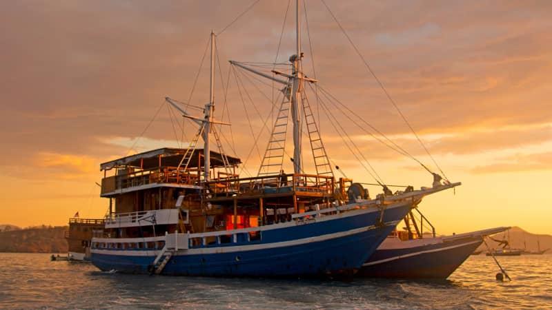 A phinisi dive boat, anchored in a Labuan Bajo marina.