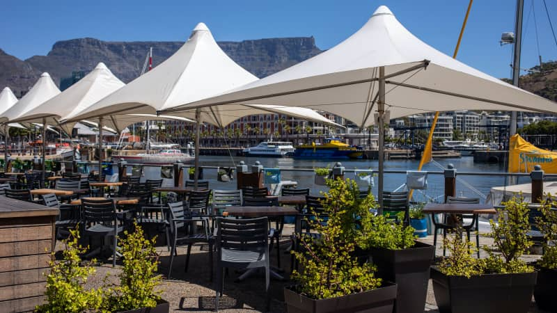 Empty tables at a restaurant terrace area in the Victoria & Alfred Waterfront in Cape Town.