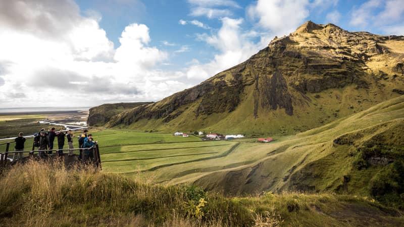 Tourists watch Skogafoss waterfall on September 2, 2018 near Skogar, in South Iceland