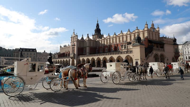 Horse carriages stand near the Cloth Hall building in the old city center in Krakow on Febuary 5, 2020.