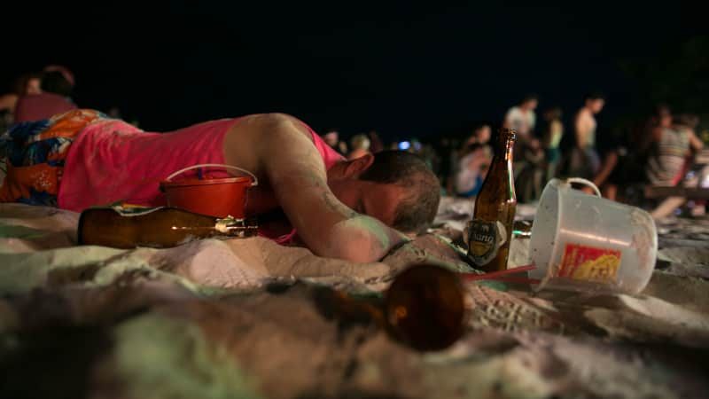 A man sleeps on the beach just before sunrise at the Full Moon Party on Haad Rin beach in 2013.