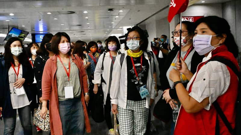 Travelers on the inaugural Taiwan-to-Palau flight gather at Taipei's airport ahead of their trip.