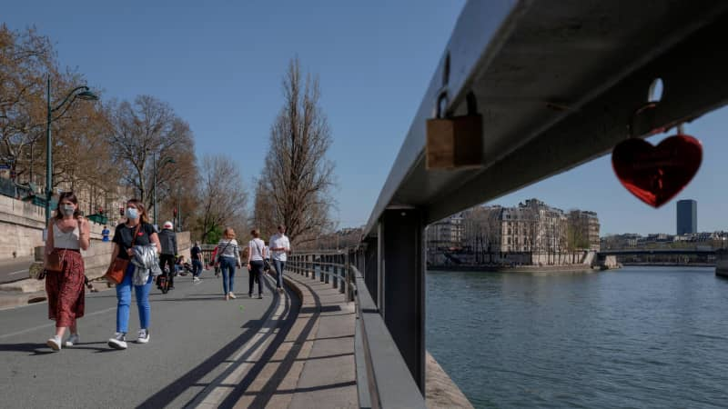 People enjoy warm weather along the banks of the Seine in Paris on March 31. Hospitalizations are ticking up in the city and vaccine rollout has been slow in France.