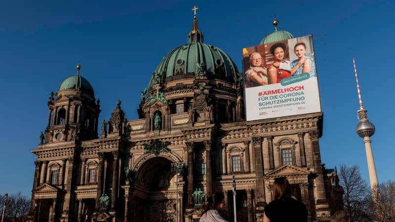 A vaccine campaign poster hangs at Berlin Cathedral in Germany. Some American expats living in Europe have been frustrated with the slow vaccine rollout and are heading back to the US for their shots.