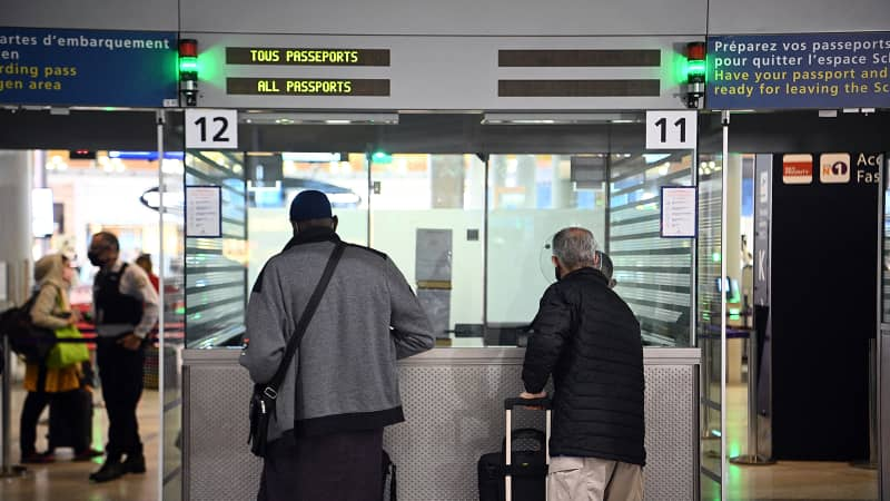 Travellers shows their documents to a border police officer at the immigration desk of Roissy Charles-de-Gaulle international airport, on February 1, 2021.