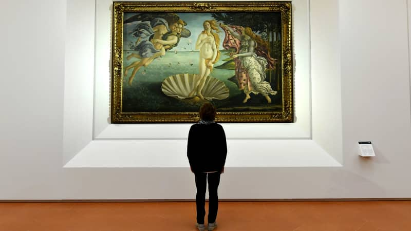 """A journalist looks at """"The birth of Venus"""" painted in the mid 1480s by Italian painter Sandro Botticelli during a press preview for the reopening of the rooms dedicated to Pollaiolo and Botticelli, at the Uffizi Gallery in Florence, on October 17, 2016. The articulation of the space has been reorganized for to faciliate the visit thanks to a large donation by the """"Friends of Florence Foundation"""". / AFP / ALBERTO PIZZOLI / RESTRICTED TO EDITORIAL USE - MANDATORY MENTION OF THE ARTIST UPON PUBLICATION - TO ILLUSTRATE THE EVENT AS SPECIFIED IN THE CAPTION (Photo credit should read ALBERTO PIZZOLI/AFP via Getty Images)"""