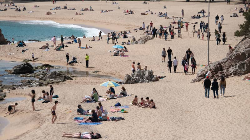 People enjoy a sunny day on the Sa Conca beach in Castell-Platja D'Aro near to Girona, on March 31, 2021.