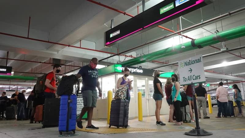 People wait in line at Enterprise rental agency in the Miami International Airport Car Rental Center in April 2021 in Florida.