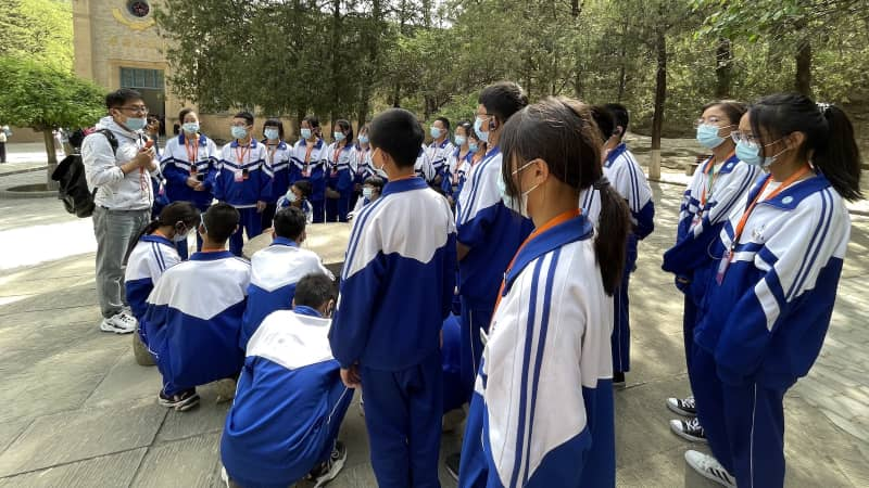 Students in school uniforms receive an open-air lecture on the Communist Party's early days in front of a historical building in Yan'an.