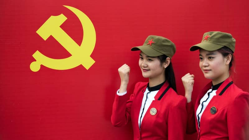 Tourists pose in front a flag of the Communist Party in Shaoshan, in central China's Hunan province in 2016.