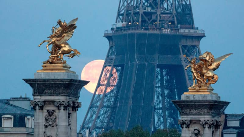 A supermoon sets behind the Eiffel Tower in Paris on April 27, 2021. France has also eased restrictions for some overseas visitors.