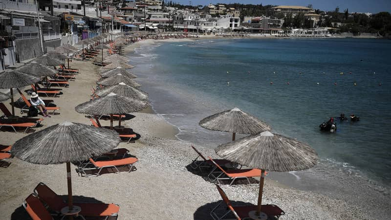Umbrellas on a beach at Agia Pelagia on the Greek island of Crete were ready for tourists on May 14, 2021. Greece has eased restrictions for some international visitors while EU-wide policies are still being finalized.