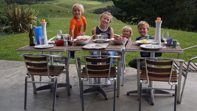 Homeswapping - The Watkins eating breakfast outside a house in Coopers Beach, Northlands, New Zealand