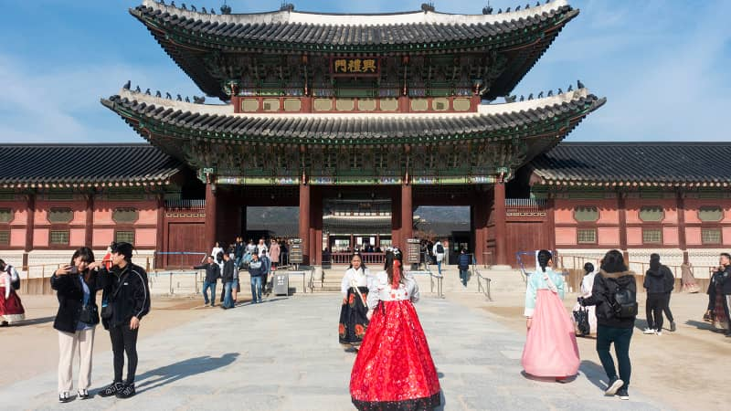 Travelers, some of whom are wearing traditional hanboks, gather in Seoul.