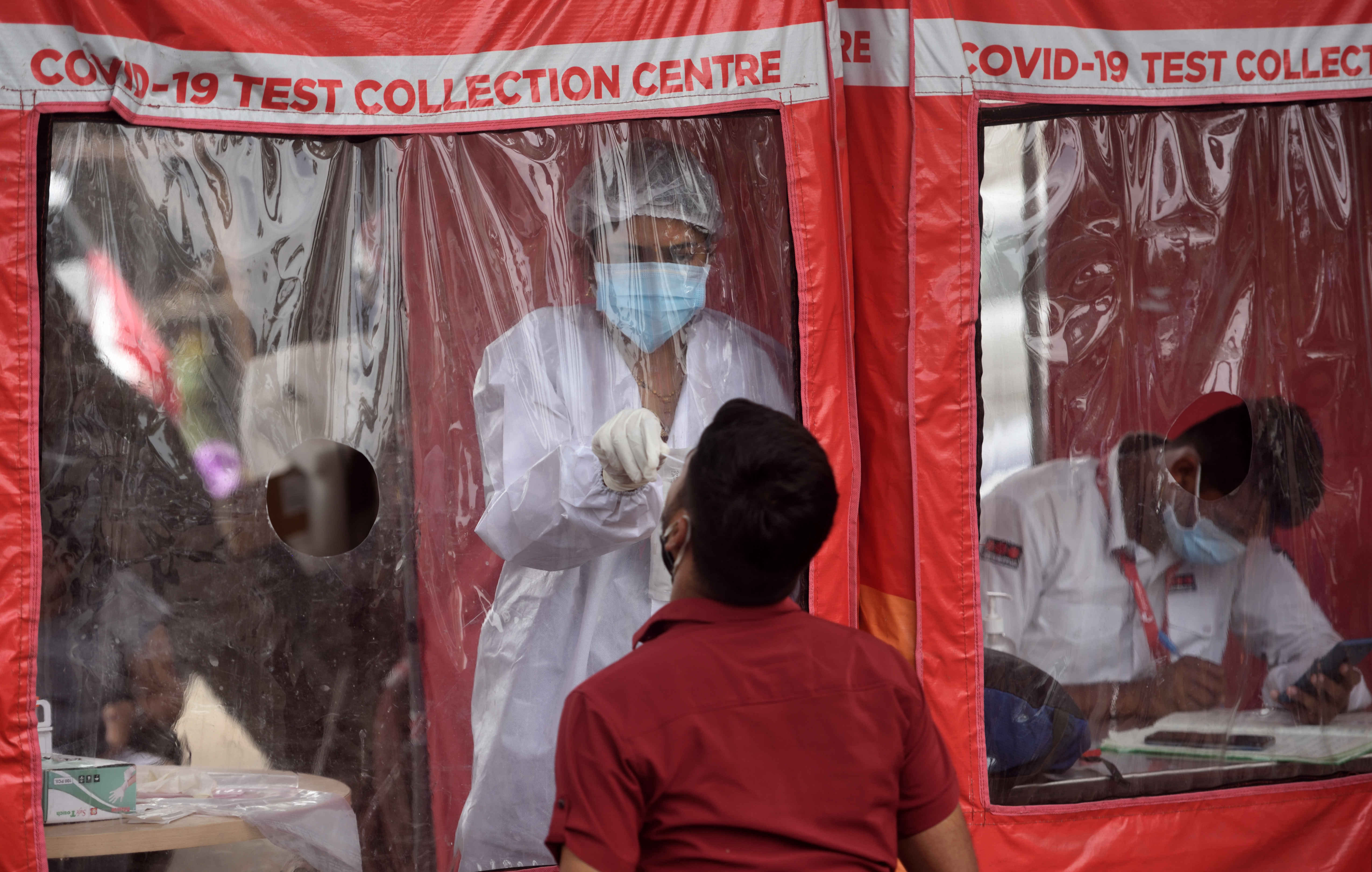 A health care worker collects a swab sample at a Covid-19 testing center in Mumbai, India, on April 22.