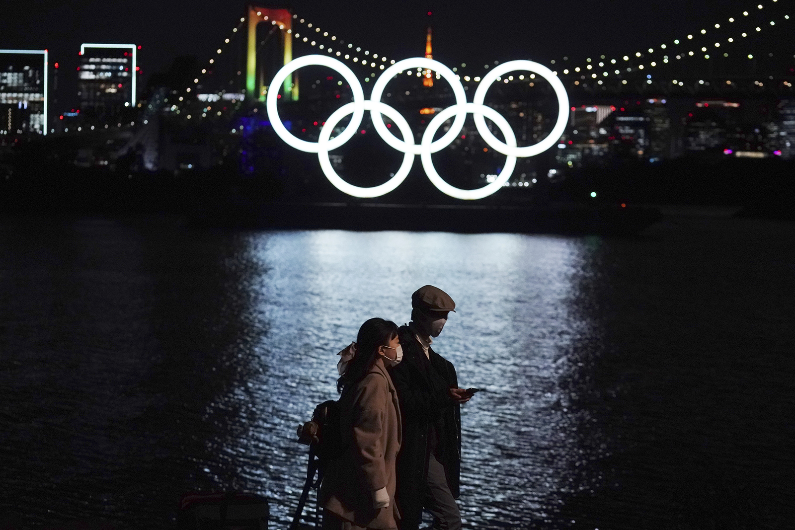 A man and a woman walk near the Olympic rings floating in the water on Dec. 1 in the Odaiba area of Tokyo.