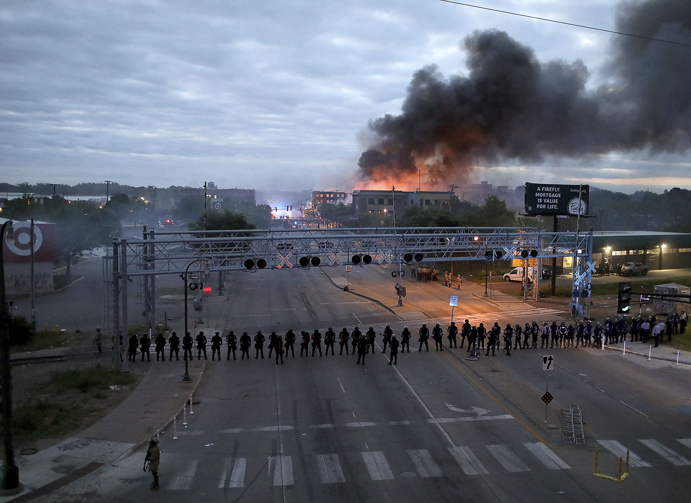 Law enforcement officers gather in Minneapolis, Minnesota, on May 29, as fires burn after a night of unrest.
