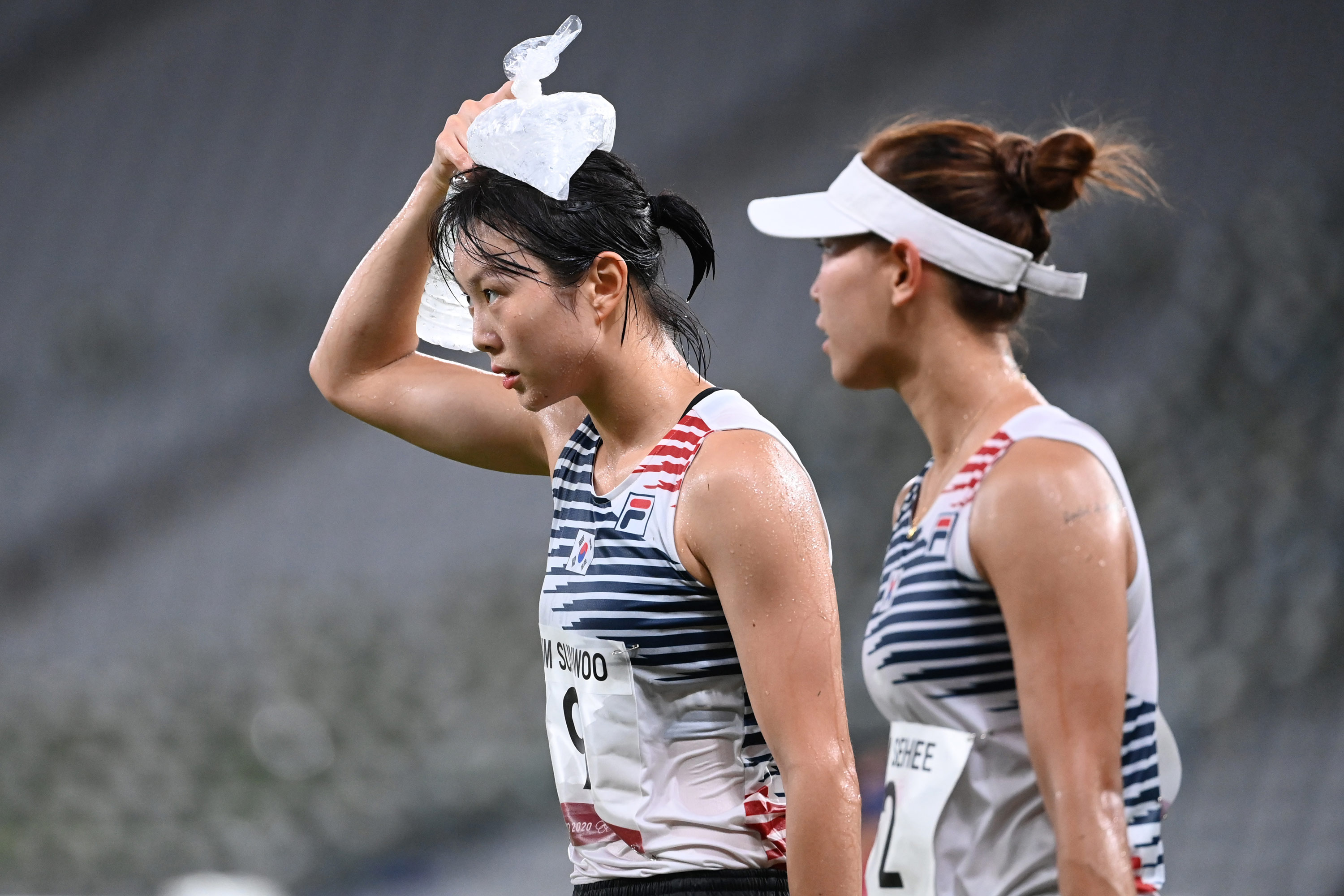 South Korea's Kim Sunwoo, left, cools her head with an ice pack during the modern pentathlon on August 6.