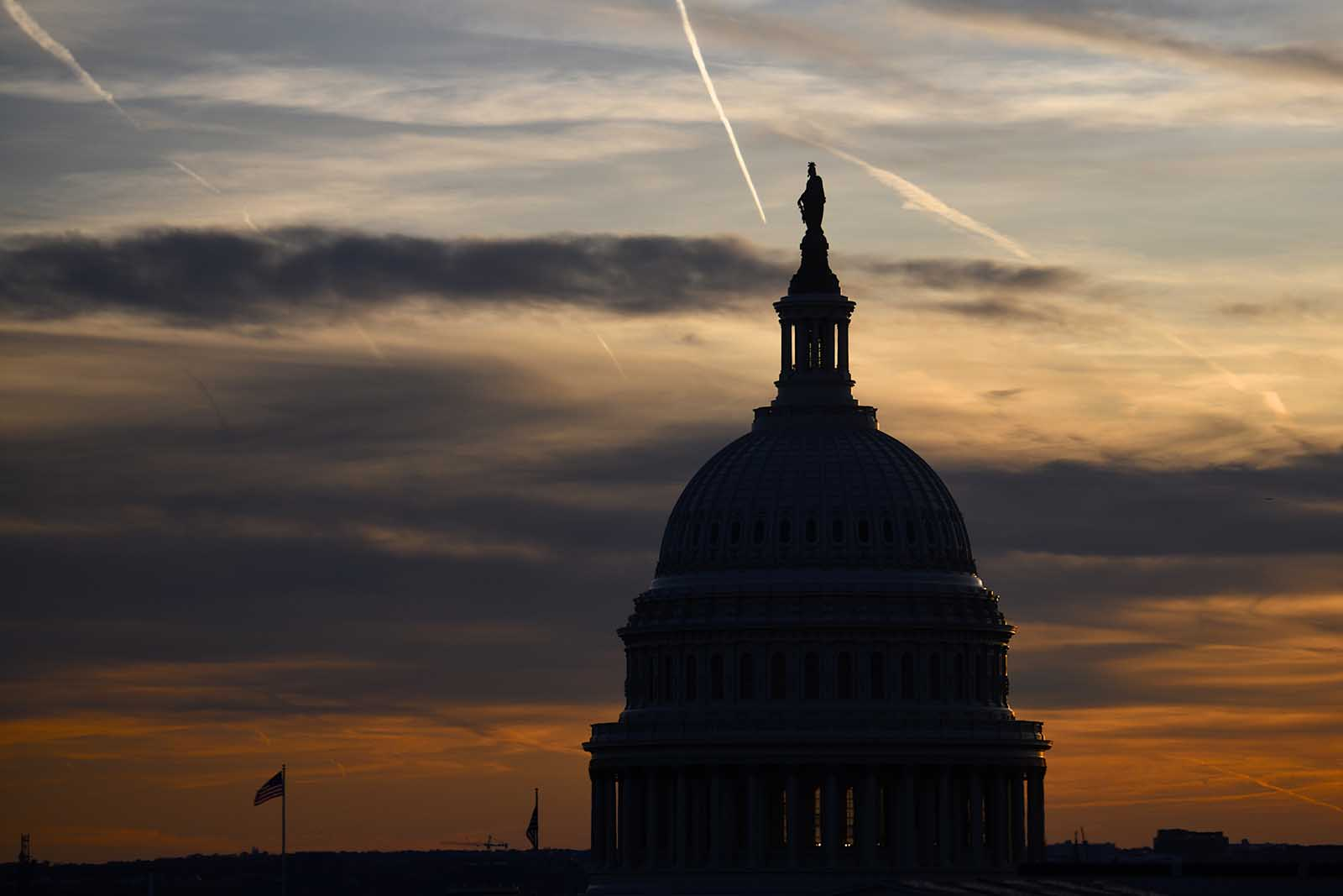 Streaks in the sky form at sunset behind the U.S. Capitol Building on November 13, 2019 in Washington.