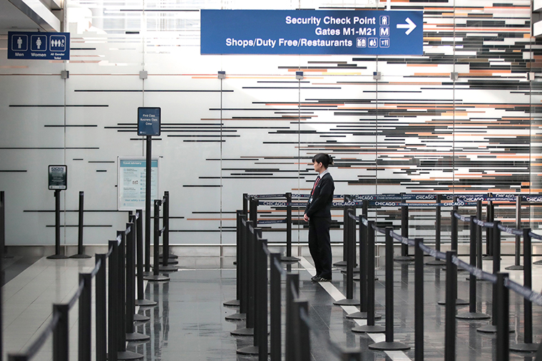worker staffs a security checkpoint in the international terminal at O'Hare Airport on March 12,  in Chicago, Illinois.