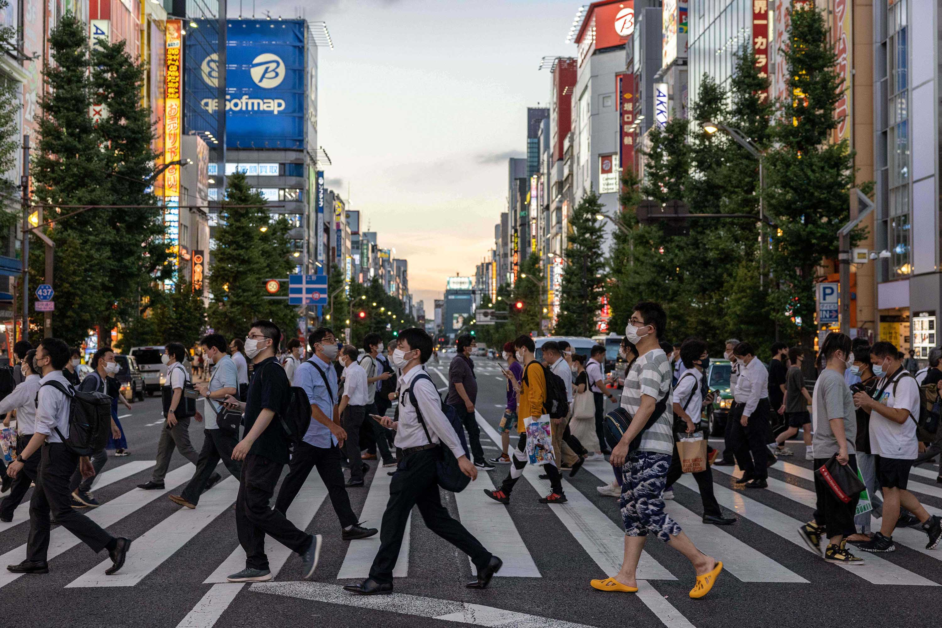 Pedestrians cross a street in the Akihabara district of Tokyo on August 4, as a coronavirus state of emergency remains in place until August 31.