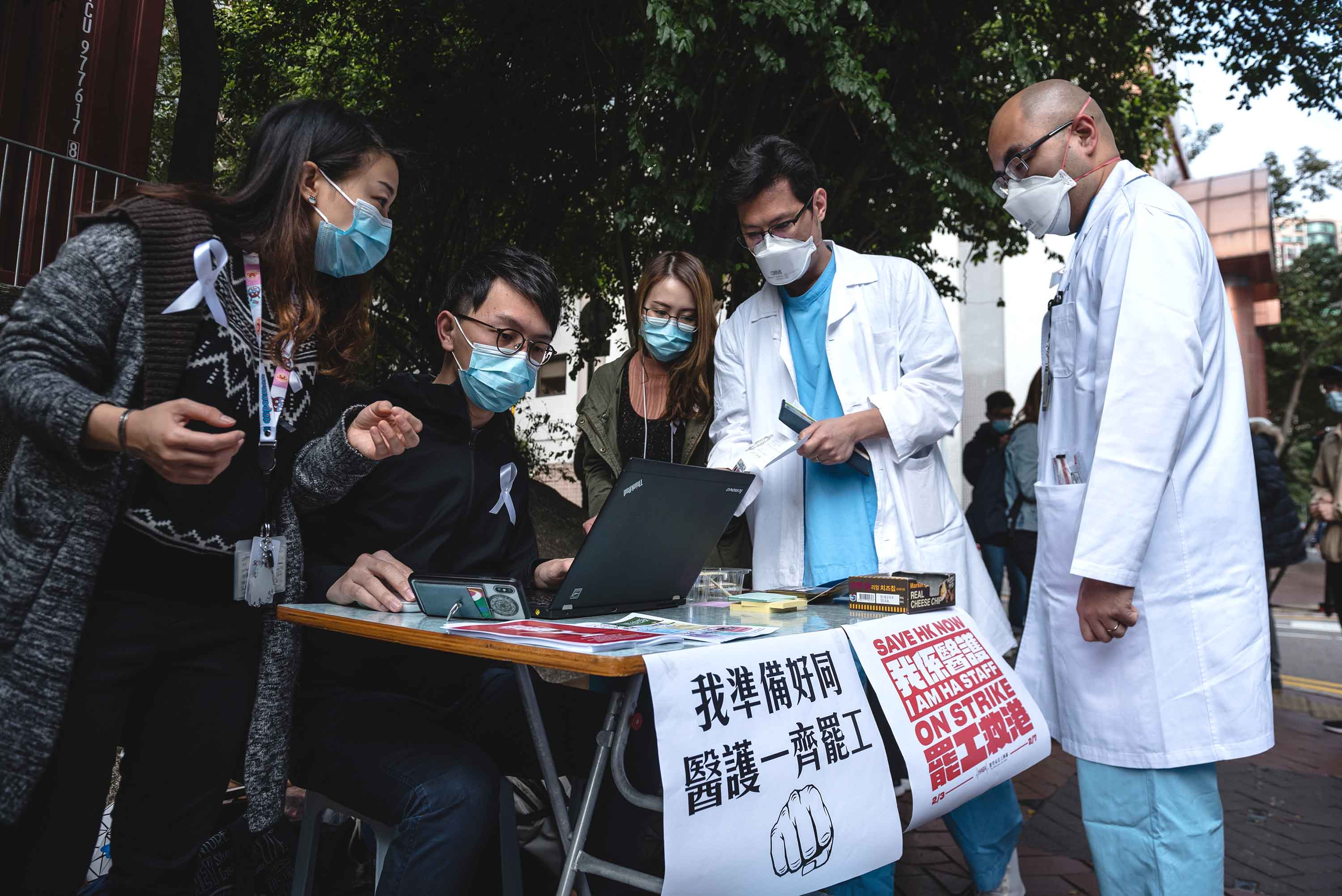 Doctors register for the medical workers strike in support of border closures at the Queen Elizabeth Hospital in Hong Kong on Monday.