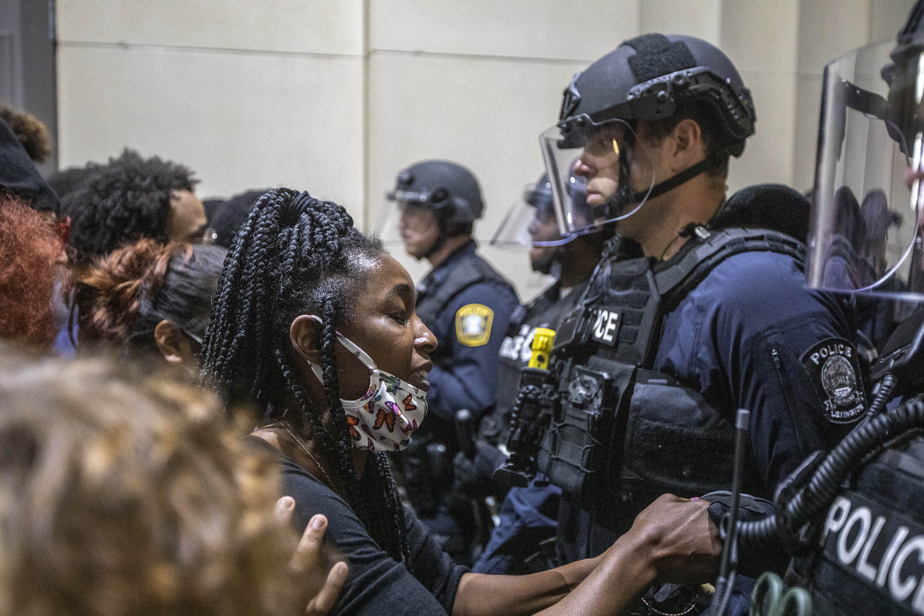 A protester holds a police officer's hand while praying together during a rally to protest the deaths of George Floyd and Breonna Taylor in Lexington, Kentucky, on Sunday, May 31.