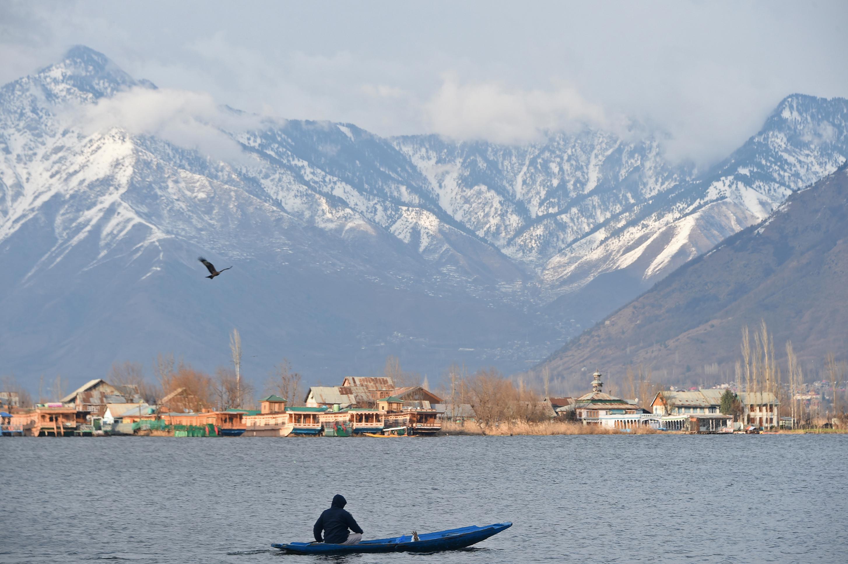 A Kashmiri man paddles his boat in Dal Lake in Srinagar on February 26, 2019.