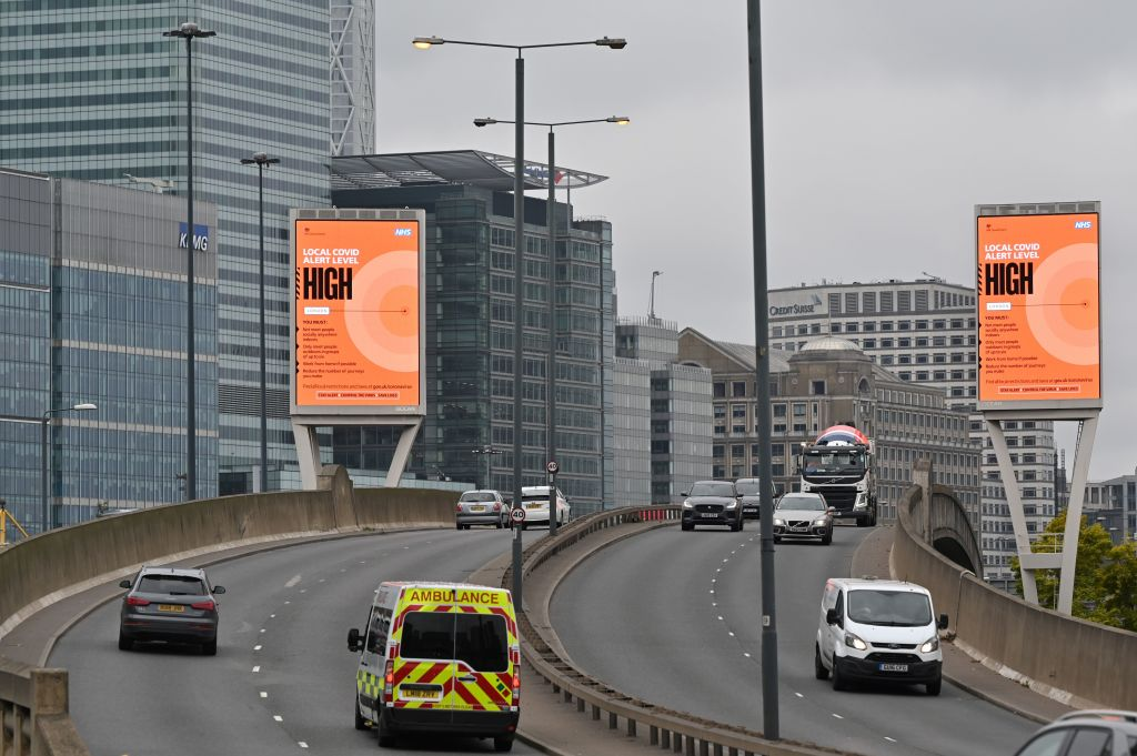 Billboards in London warn commuters of a rise in local infections.